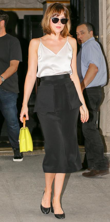 Dakota Johnson wears black and white outfit while carries her green purse in New York City Pictured: Dakota Johnson Ref: SPL1121375 090915 Picture by: Felipe Ramales / Splash News Splash News and Pictures Los Angeles: 310-821-2666 New York: 212-619-2666 London: 870-934-2666 photodesk@splashnews.com